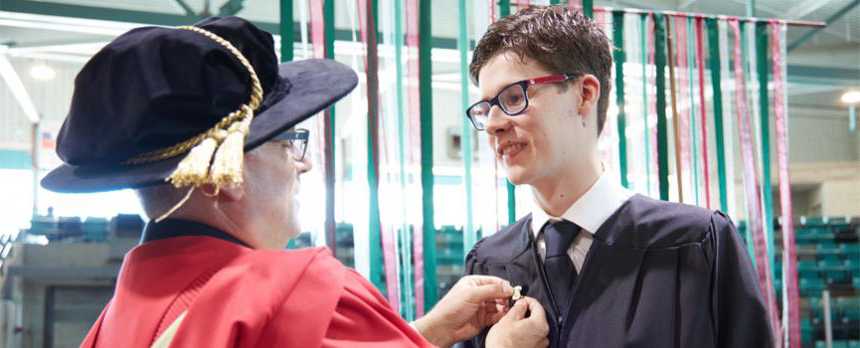 VP Academic and Dean pinning investiture pin onto a student