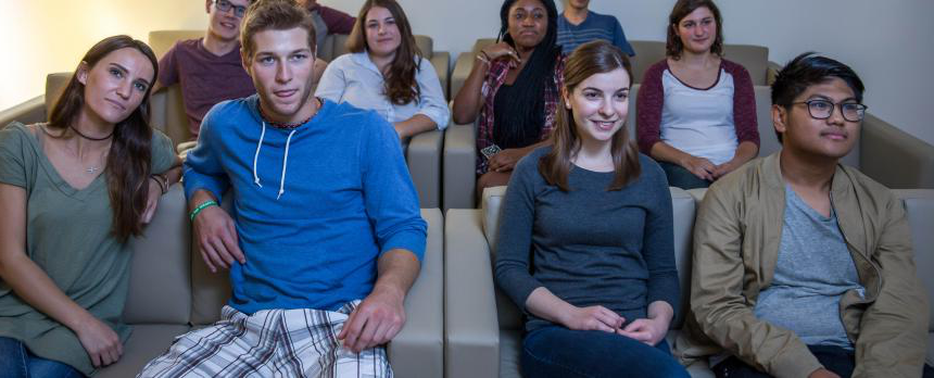 Image of students seating on sofa and watching screen